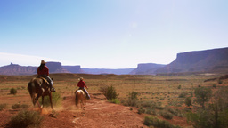 Shot of a man and woman riding horses in the Moab Desert in Utah with lens flare Footage