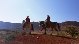 Shot of man and woman riding horses along the Moab Valley in Utah with lens flar Footage