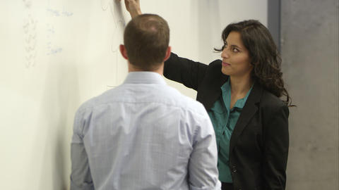 Panning shot of woman talking with coworker and writting on whiteboard Footage