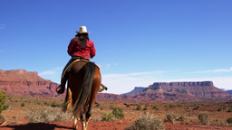 Shot of two people riding horses in the Moab Valley in Utah Footage