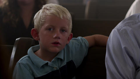Young, blonde-haired boy sitting on a bench at church Footage