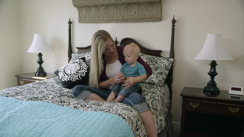 Mom playing with baby on the bed Footage