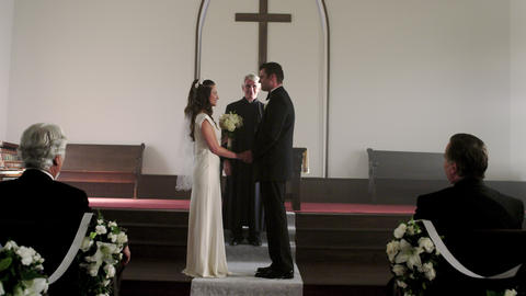 Preacher talking to a bride and groom in a chapel Footage