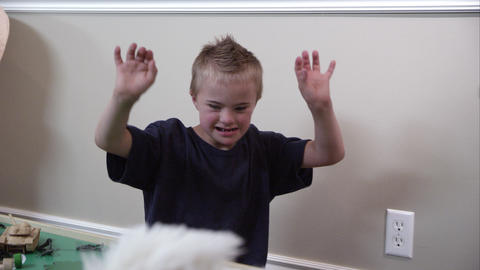 Downs syndrome boy throwing a white stuffed animal Footage