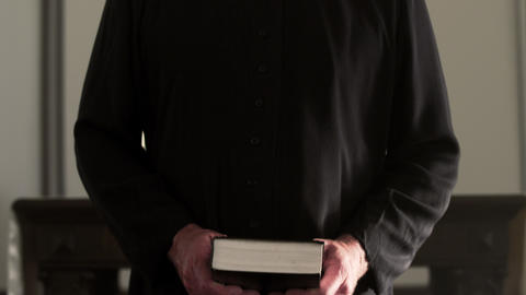 Preacher standing, waiting, and holding a book Footage