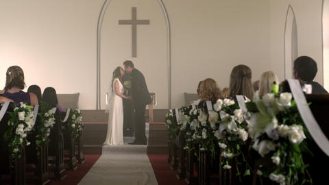 Bride and groom at the front of a chapel with a preacher Footage