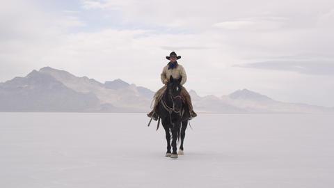 Cowboy riding horse on salt flats Live Action