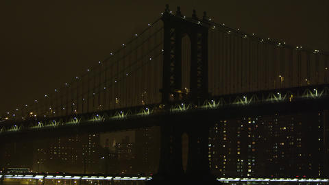 Static zoomed view at night overlooking the East River and the Manhattan Bridge Footage