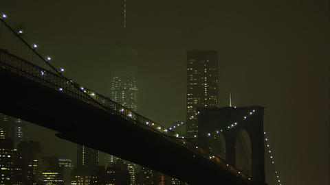 Static zoomed view at night overlooking the East River and the Brooklyn Bridge Footage