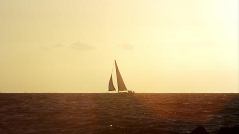 Static zoomed view of sailboat on the horizon at sunset Footage