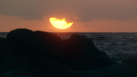 Zoomed slow motion shot of sun setting over the ocean Footage