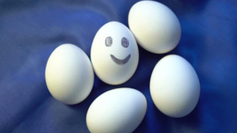 Pile of eggs, one smiling, different, standing out from faceless the crowd Footage