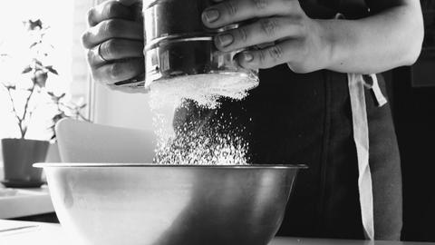 Woman sifting flour in a bowl Footage