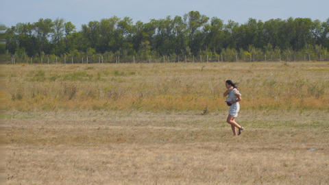 Girl walks across a field with dry grass Footage