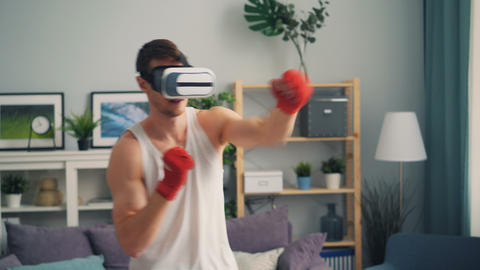 Young man in modern augmented reality glasses boxing in apartment training alone Footage