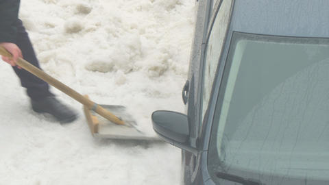 Man digs a shovel of snow from a car stuck in the snow Live Action