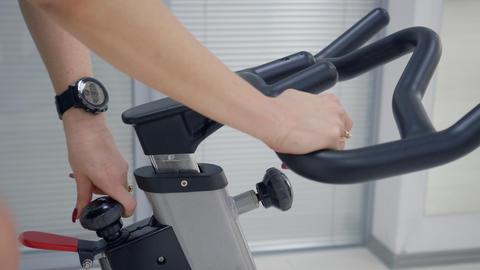 Hands of fitness woman holding handlebar indoor bike adjusting while training Live Action