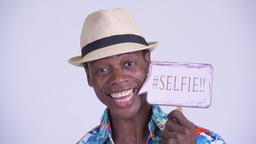 Face of young happy African tourist man smiling with selfie paper sign Archivo