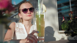 Business Lady in Sunglasses is Drinking Cocktail with Straw in Cafe in Summer Footage