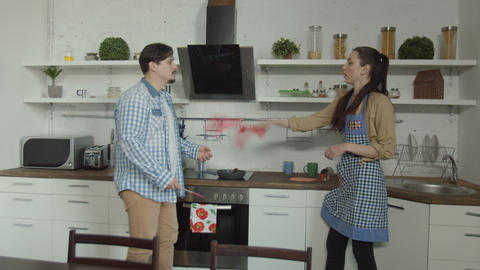 Couple arguing over uncooked food in kitchen Live Action