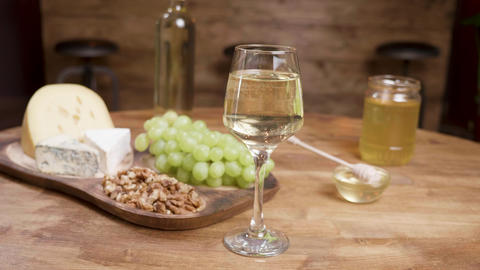 Cheese appetizers on a wooden table with wine and grapes ライブ動画