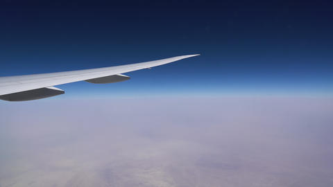 The plane flies in the stratosphere. The plane wing and the blue sky over a Live Action