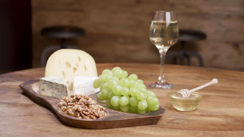 Cheese and grapes on a wooden table with honey, walnuts and wine ライブ動画