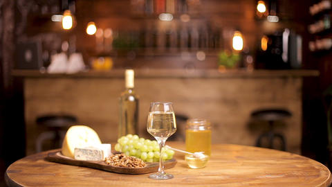 Beautiful composition of cheeses served with wine on wooden table ライブ動画