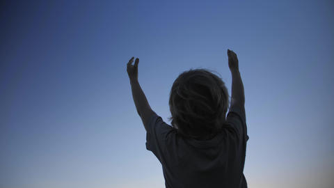 Child silhouette raising hands up in the air on blue sky background Live Action
