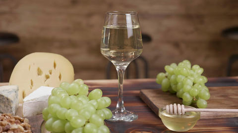 A composition of cheeses and a glass of white wine in the center ライブ動画