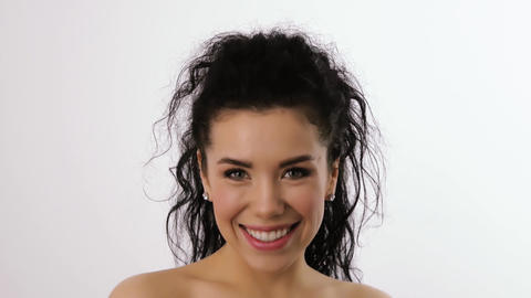 Portrait of a woman with curly hair smiling in studio Footage