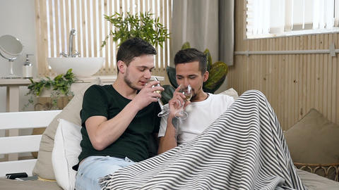 Caucasian gay couple are drinking white wine lying in the bed at home. Gay Footage
