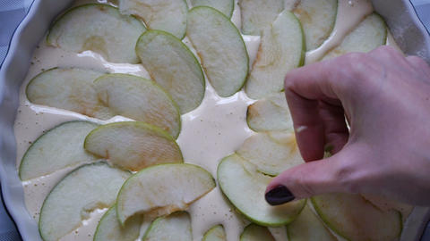 Woman making apple pie. Cook puts apple slices into baking pan. Sliced apples on Footage