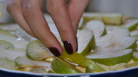 Close up. Woman making apple pie. Cook puts apple slices into baking pan. Sliced Footage