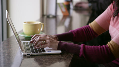 View of womans hands typing on laptop near window in coffee shop Footage