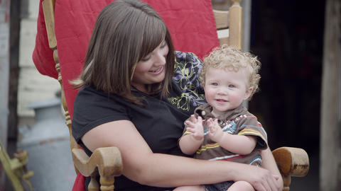 Dolly in shot of a Woman holding child in lap while rocking in a rocking chair Footage