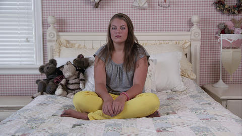 Slow motion push of teenage girl sitting on bed Live Action