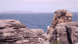 Cliffs of rocks with an island and the ocean behind Footage