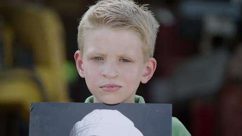 Slow motion from photo to boys face of him showing photo with cleft palate Footage