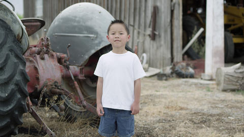 Slow motion push of young boy standing and smiling near tractor Footage