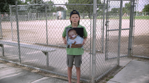 Slow motion push of boy standing and holding up picture of himself as baby Filmmaterial