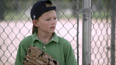 Slow motion of boy looking to the side as he hits his baseball mitt Footage