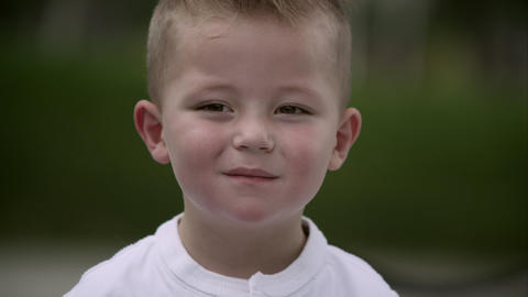 Up close slow motion of young boy trying to hold his smile back Footage
