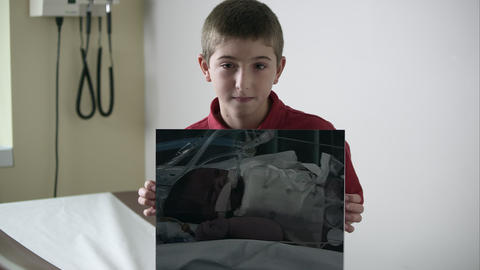 Slow motion of young boy holding up photo of himself as a baby in the hospital Footage