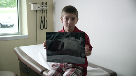 Slow motion push of young boy holding photo of himself as baby in hospital Footage