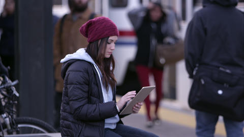 Woman using tablet as people are walking around her Footage