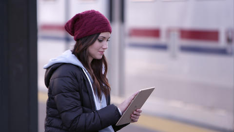 Woman swiping on tablet as she sits at transit station Footage