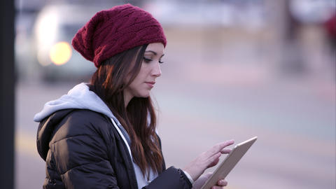 Woman looking around then starts using tablet Footage