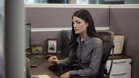 Up close panning view of woman in cubicle using computer Footage