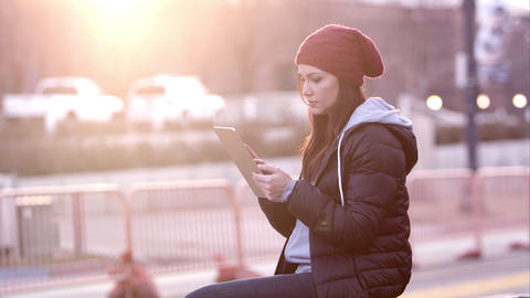 Woman using tablet as she sits near the road in Footage